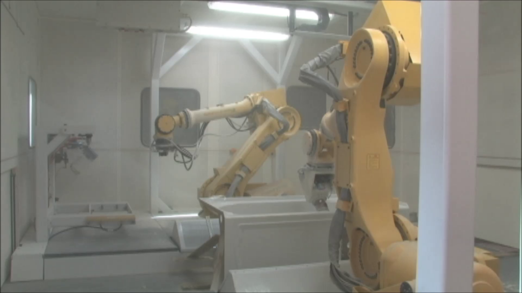Two robots drill and trim composite Kohler bathtub in workcell