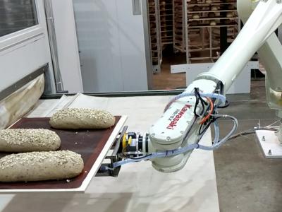 Kawasaki Robot loading a tray of dough into an oven