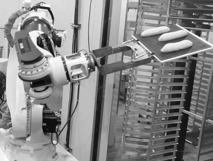 Robot placing rack of bread dough on bakery racks